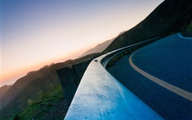 Asphalt road, fence, mountains, dusk HD wallpaper