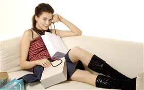 Girl sit on sofa, shopping bags HD wallpaper
