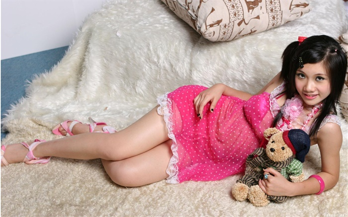 Smile pink dress Asian girl, bed, toy Wallpapers Pictures Photos Images