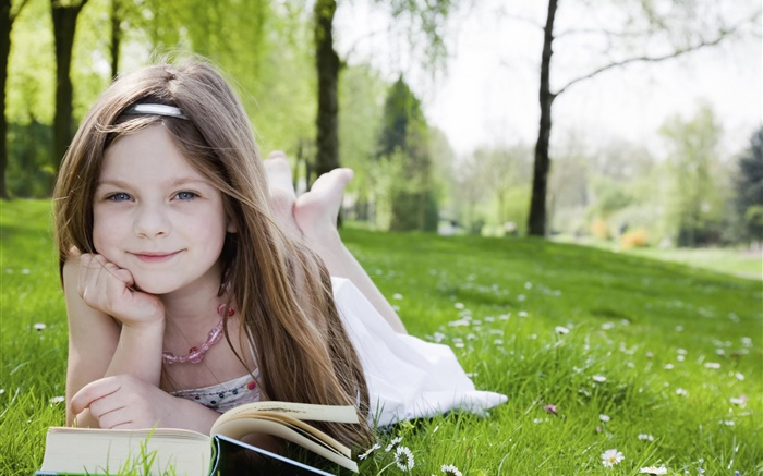 Cute little girl in the grass, read book Wallpapers Pictures Photos Images